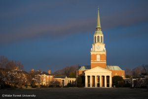 The early morning sun lights Wait Chapel against dark clouds over the Wake Forest campus